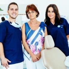 Dr. Varajti Artúr fogorvos és szájsebész és fogászati asszisztens között áll a páciens